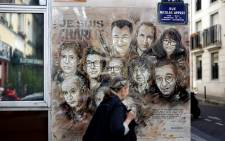 A woman walks past a painting by French street artist and painter Christian Guemy, known as C215, in tribute to members of 'Charlie Hebdo' newspaper who were killed by jihadist gunmen in January 2015, in Paris, on 31 August 2020. Picture: AFP