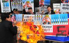 FILE: South Korean conservative activists burn a North Korean flag during a rally denouncing North Korea's missile test-launch in Seoul on 26 March, 2014. Picture: AFP.