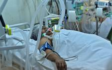 A Tunisian patient infected with COVID-19 is pictured at the intensive care unit of the Aghlabide hospital in the east-central city of Kairouan on 4 July 2021. Tunisia placed the capital Tunis and the northern town of Bizerte under a partial lockdown from until 14 July in a bid to rein in record daily coronavirus cases and deaths. Picture: FETHI BELAID/AFP