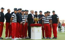 US President Donald Trump poses with the US Team and the trophy after they defeated the International Team 19 to 11 in the Presidents Cup at Liberty National Golf Club on 1 October, 2017 in Jersey City, New Jersey. Picture: AFP.
