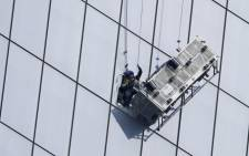 A window washer is seen being rescued by NYPD and NYFD rescue after his carriage came dislodged from his cables alongside the One World Trade Center in New York on 12 November 2014. Picture: EPA