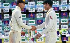 England's captain Joe Root (L) and Australia's captain Tim Paine shake hands alongside the Ashes trophy during the presentation ceremony on the fourth day of the fifth Ashes cricket Test match between England and Australia at The Oval in London on 15 September 2019. England won the fifth test by 135 runs and drew the series but Australia keeps The Ashes trophy. Picture: AFP