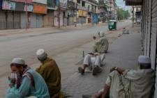 Labourers sit outside shuttered shops in a closed commercial market area during lockdown, following new restrictions imposed as a preventive measure against the spread of the Covid-19 coronavirus, in Peshawar May 2, 2021. Picture: Majeed / AFP.