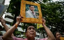 A supporter of Thailand's King Bhumibol Adulyadej holds a picture bearing his image at Siriraj Hospital, where the king was being treated, in Bangkok on 13 October 2016. Picture: AFP.