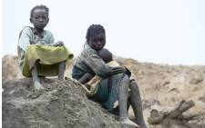 Children gold miners sit on 5 May, 2014 next to a traditional mine in the village of Gam where gold mining is the main business activity. Picture: AFP