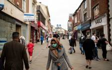 In this file photo taken on 30 July 2020 Pedestrians wear facemasks as they walk through a pedestriansed street in Oldham, greater Manchester, northwest England on 30 July 2020. Picture: AFP
