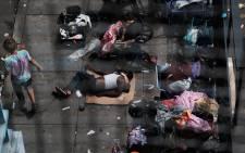 People gather on a street overtaken by heroin users in Kensington on 19 July 2021 in Philadelphia, Pennsylvania. Picture: AFP