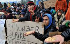 Migrants and refugees hold a placard (C) reading on hunger strike they wait to cross the border between Greece and Macedonia near the Greek village of Idomeni on November 21, 2015. Picture: AFP.