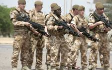 "FILE. British soldiers pose for a photograph along the parade ground in Baghdad's fortified ""Green Zone"" on 16 May 2009. Picture: AFP."