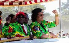 FILE: Zimbabwe President Robert Mugabe with his wife Grace Mugabe raising their fists in a vehicle before meeting delegates during a Zimbabwe ruling party Zanu-PF youth rally at Rudhaka Stadium in Marondera on 2 June 2017. Picture: AFP.