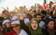 People cheer as Turkey's main opposition Republican People's Party (CHP) leader Kemal Kilicdaroglu throws flowers to supporters during a rally on 9 July 2017 in Istanbul. Picture: AFP