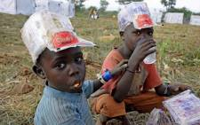 Newly arrived refugee children from South Sudan eat and drink at the Ngomoromo border post, in Ugandan side, on 10 April 2017. Picture: AFP.