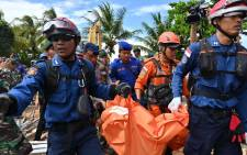 "Members of an Indonesian search and rescue team carry a body bag taken from the Villa Stephanie accommodation in Carita in Banten province on 24 December 2018, two days after a tsunami - caused by activity at a volcano known as the ""child"" of Krakatoa - hit the west coast of Indonesia's Java island. Picture: AFP"