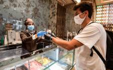 A customer buys takeaway ice cream at the Venchi ice cream parlour on 4 May 2020 in Milan as Italy starts to ease its lockdown. Picture: AFP