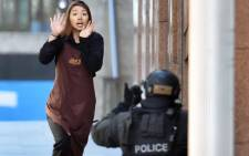 One of the hostages runs towards police from a cafe in the central business district of Sydney on 15 December 2014. Picture: AFP.