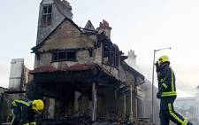 Firemen douse the charred remains of the Reeves furniture store in Croydon, south of London, on August 9, 2011. Picture: AFP