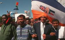 Miles Bhudu (L),head of the South African Prisoners Organisation for Human Rights, Rashied Staggie (2ndL), leader of the Hard Living Kids gang, Pastor Alben Martins(2ndR), a reformed gangster and a church associate walk underneath the South African flag during a march to Parliament in Cape Town 22 September, 1996. Picture: AFP