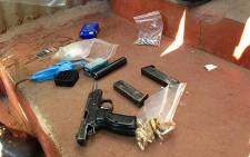 A 9mm pistol, ammunition and an AK47 rifle were recovered during a raid in Alexandra. Picture: Lesego Ngobeni/EWN