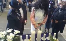 The widow of Lieutenant Colonel Charl Kinnear lights a candle at a memorial service for his husband on 30 September 2020 held in Belhar. Picture: @SAPoliceService/Twitter