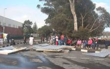FILE: Imizamo Yethu residents sit on the roadside after blocking the roads with sheets of corrugated iron. Picture: Bertram Malgas/EWN.
