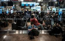 Travellers wait for their trains at the Lyon Part-Dieu railway station, on the first evening of a two days strike, on 2 April, 2018 in Lyon. Picture: AFP