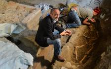 """Italian archaeologist Silvano Vincenti (R) sits alongside another archaeologist working on the third excavation of a grave inside the medieval Convent of Saint Ursula in Florence on July 17, 2012, during research focusing on the burial site of Lisa Gherardini, wife of the wealthy Florentine silk merchant Francesco del Giocondo, the model who inspired Leonardo da Vinci's painting """"The Mona Lisa"""". AFP PHOTO / ANDREAS SOLARO"""