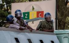 Police officers patrol at the Zimbabwe Electoral Commission offices in the capital as Zimbabwe's main opposition parties demonstrate in support of free and fair elections to be monitored by international bodies on 22 March 2017 in Harare, Zimbabwe. Picture: AFP