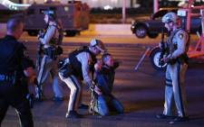 Police officers stop a man who drove down Tropicana Avenue near Las Vegas Boulevard and Tropicana Avenue, which had been closed after a mass shooting at a country music festival on 2 October 2017 in Las Vegas, Nevada. Picture: AFP.