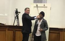 FILE: Jason Rohde demonstrating to the court how a hair iron cord was placed around his wife, Susan. Picture: Shamiela Fisher/EWN