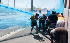 FILE: People taking part in a protest against poor sanitation run away from a water cannon and stun grenades fired by members of the South African Police Services in Cape Town. Picture: AFP.