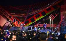 Rescue workers gather at the site of a metro train accident after an overpass for a metro partially collapsed in Mexico City on May 3, 2021. At least 13 people were killed and dozens injured in a metro train accident in the Mexican capital on May 3, the authorities said. Picture: Pedro Pardo / AFP