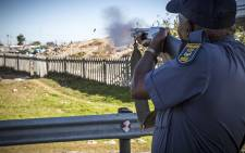 A policeman fires rubber bullets at protesters on the N2 inbound outside Khayelitsha in Cape Town after land grabbers and police clashed during violent evictions. Picture: Thomas Holder/EWN