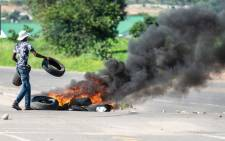 "A protester burns tyres on a road during a ""stay-away"" demonstration against the doubling of fuel prices on 14 January 2019 in Emakhandeni township, Bulawayo. Picture: AFP"