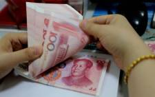 A teller counts yuan banknotes in a bank in Lianyungang, east China's Jiangsu province. Picture: AFP.