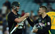 Australia's not out pair Cameron White (L) and Pat Cummins celebrate victory against South Africa in the 3rd and final T20 cricket match played at the ANZ Stadium in Sydney on 9 November, 2014.