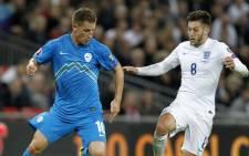 England's midfielder Adam Lallana (R) is challenged by Slovenia's midfielder Valter. Picture: AFP