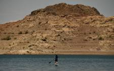 FILES) In this file photo taken on July 21, 2021 a paddle boarder rides with a dog during low water levels due to the western drought at the Lake Mead Marina on the Colorado River in Boulder City, Nevada. A huge reservoir that supplies water to tens of millions of people in the Western US is at such low levels that populations it feeds must reduce their useage next year, the government said August 16. A chronic drought has left huge swathes of the country parched