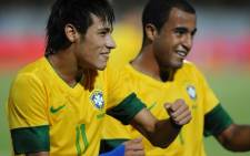 Brazilian footballer Neymar (L) dances with teammate Lucas after scoring against China in a friendly match held at the Arruda stadium in Recife, northern Brazil, on 10 September, 2012. Picture: AFP.
