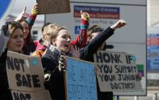 Demonstrators and junior doctors hold placards as they protest outside the Basingstoke and North Hampshire Hospital, in Basingstoke, west of London, on 26 April 2 2016, during a strike by junior doctors. Picture: AFP.