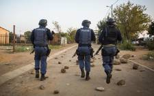 Police search through the streets of Lichtenburg in the North West for protesters following unrest in the area over service delivery. Picture: Reinart Toerien/EWN