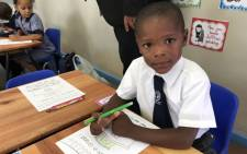 A grade 1 pupil gets settled in at the Forest Village Leadership Academy in Eerste River, Cape Town on 9 January 2019. Picture: Lauren Isaacs/EWN