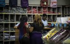 Parents purchasing school uniforms and supplies for their children the day before schools reopen.
