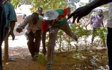 Journalists flee the national television headquarters as gunshots are fired around the premises in Ouagadougou on 2 November, 2014. Picture: AFP.