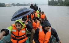 Indian fire and rescue personnel evacuate local residents in an boat flooded following monsoon rains at Aluva, in the Indian state of Kerala, on 16 August 2018. Picture: AFP