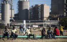 Striking platinum miners gather at the Wonderkop Stadium in Marikana waiting to receive news on an ending strike proposed deal on 12 June, 2014 in Marikana, South Africa. Picture: AFP.