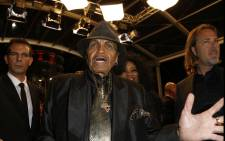 """FILE: US musician and manager Joe Jackson (C) and a guest arrive on 24 May 2013 for the screening of the film """"Michael Kohlhaas"""" presented in Competition at the 66th edition of the Cannes Film Festival in Cannes. Picture: AFP."""