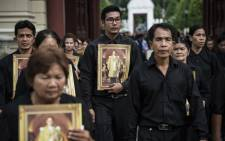 Mourners dressed in black walk through the grounds of the Grand Palace on their way to the throne hall to pay respects to the late Thai King Bhumibol Adulyadej, in Bangkok on 29 October, 2016. Picture: AFP.