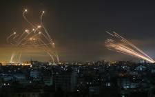 The Israeli Iron Dome missile defence system (L) intercepts rockets (R) fired by the Hamas movement towards southern Israel from Beit Lahia in the northern Gaza Strip as seen in the sky above the Gaza Strip overnight on May 14, 2021. Israel bombarded Gaza with artillery and air strikes on Friday, May 14, in response to a new barrage of rocket fire from the Hamas-run enclave. Picture: ANAS BABA/AFP