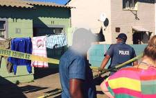 A police officer is pictured on scene where a young man was killed inside his house in Elsies River amid gang violence. Picture: facebook.com