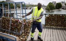 A worker removes 'love padlocks' attached on the railings of the Pont des Arts bridge in Paris on 1 June, 2015. Picture: AFP.